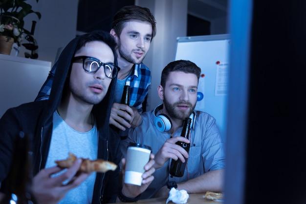 Дружеские отношения. красивый приятный коллега-мужчина пьет пиво и смотрит фильм, проводя время вместе после работы