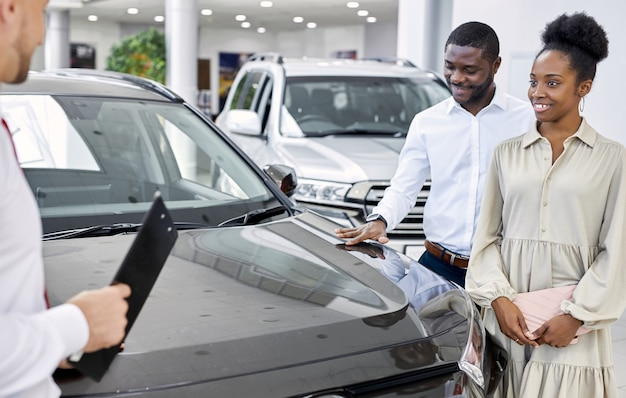Friendly salesman and beautiful african couple in car showroom