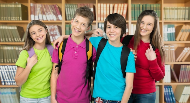 Friendly school children with backpacks on background