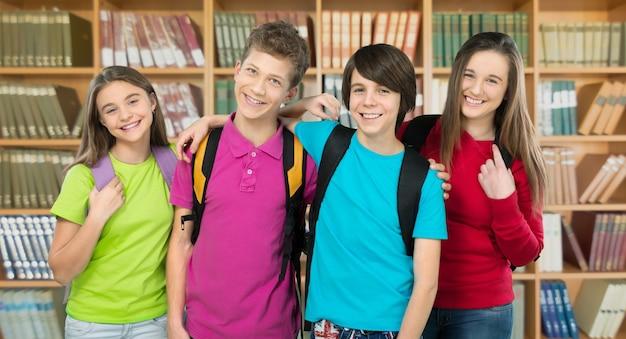 Дружелюбные школьники с рюкзаками на фоне