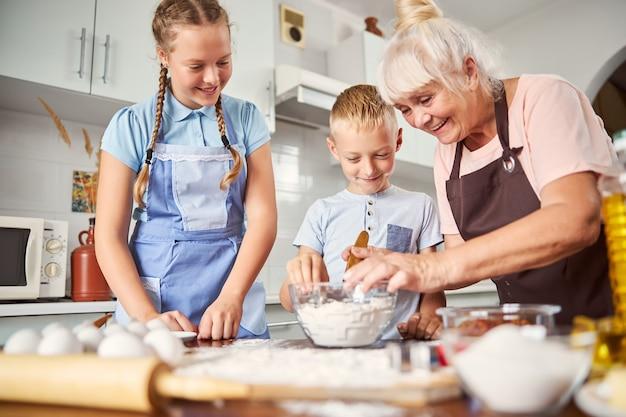 손자에게 반죽을 만드는 방법을 보여주는 친절한 노부인