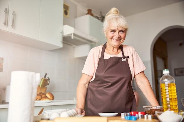 彼女の台所で笑っているフレンドリーな年配の女性