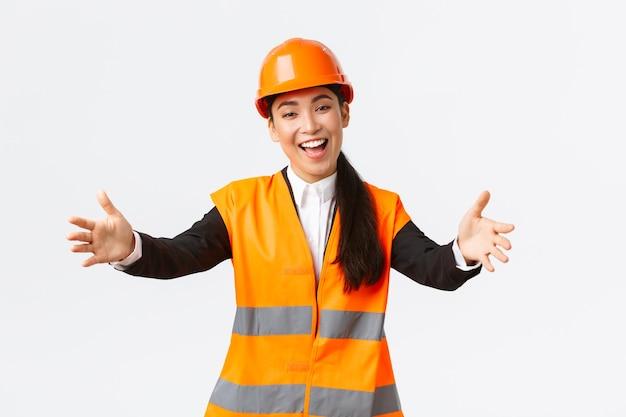 フレンドリーな笑顔のアジアの女性建設マネージャー、安全ヘルメットと反射ジャケットのエンジニア、挨拶のために手を伸ばし、ビジネスパートナーを歓迎し、白い背景に立って