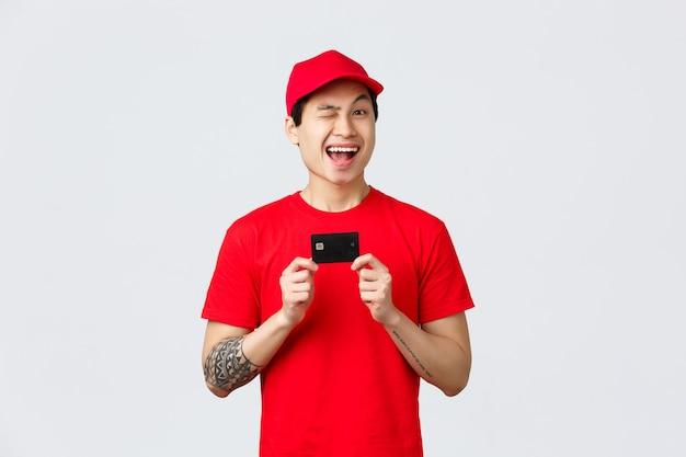 Приветливый улыбающийся азиатский мужчина в красной кепке и футболке, весело подмигивает, рекомендует использовать кредитную карту, покупать бесконтактно во время эпидемии вируса. курьер проконсультирует заказ онлайн по коронавирусу