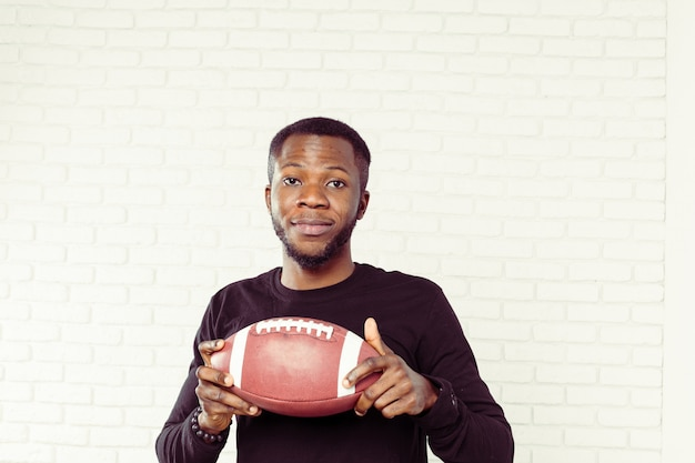 Friendly smiling black man holding a football