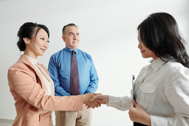 Friendly smiling business people greeting and shaking hand of new coworker after successful job interview