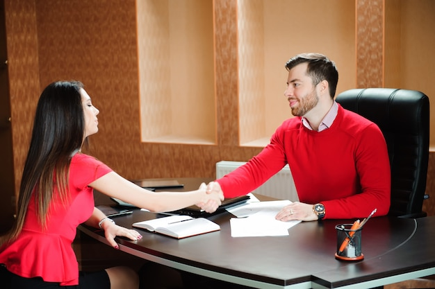 Friendly smiling businessman and businesswoman handshaking over
