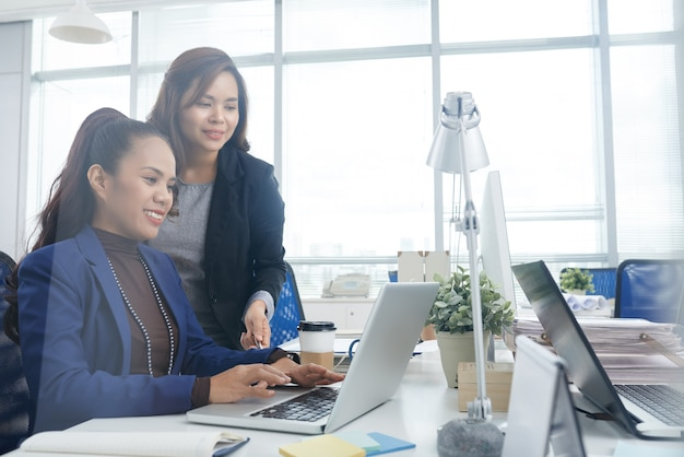 Friendly smiling businesswoman helping new coworker with filling form on laptop