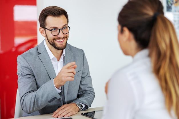 Дружелюбный, улыбающийся продавец автомобилей сидит за столом с женщиной.
