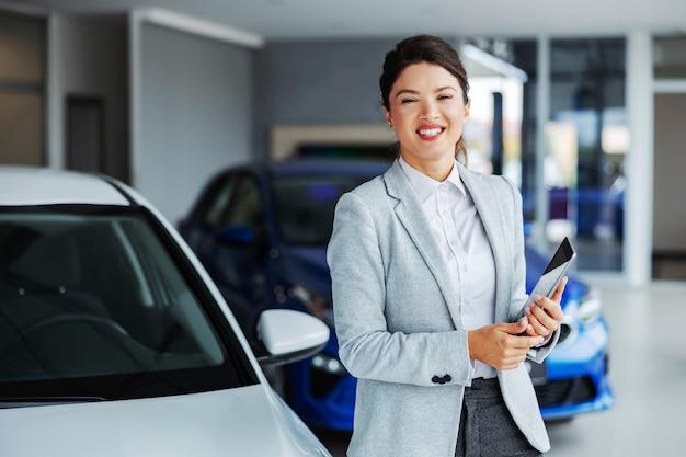 Дружелюбная, улыбающаяся женщина-продавец автомобилей стоит в автомобильном салоне и держит планшет, глядя вперед