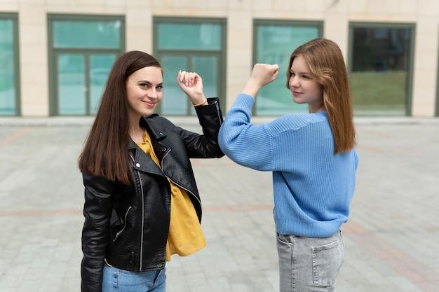 사회적 거리를 유지하는 친절한 웃는 여성, 팔꿈치를 부딪혀 서로 인사