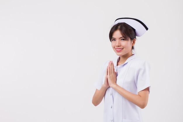 아시아 태국 스타일 환영 제스처와 함께 친절 웃는 여성 간호사