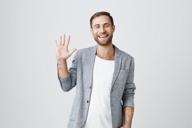 Friendly smiling handsome guy waving hand in greeting, say hello