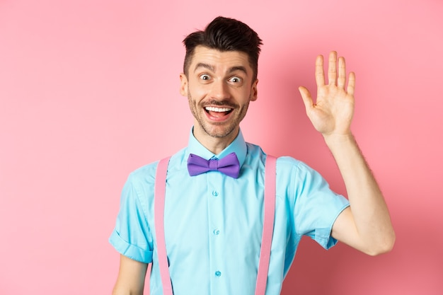 Friendly smiling man in funny bow-tie saying hello, waving hand to greet you, make hi gesture and looking happy yo see you, standing over pink.