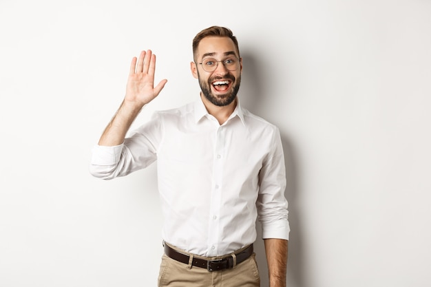 Friendly smiling man in glasses saying hello, waving hand in greeting, standing over white background.