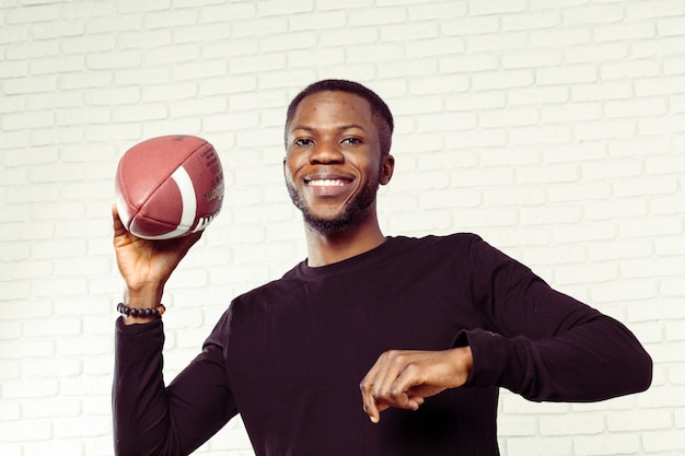 Friendly smiling man holding a football