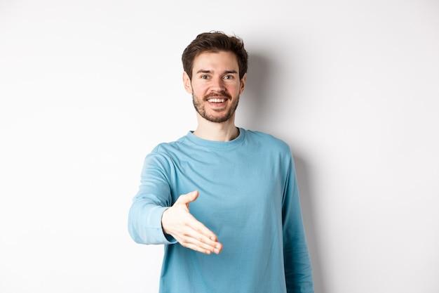 친절한 웃는 남자가 손을 뻗어 인사하고 악수를 위해 팔을주고 흰색 배경 위에 서 있습니다.