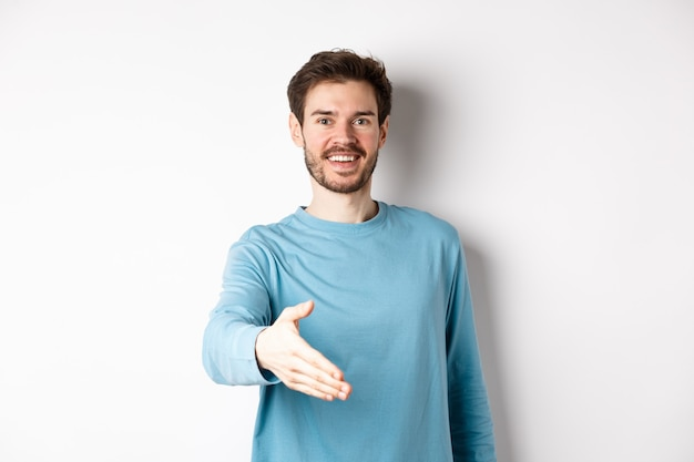Friendly smiling man stretch out hand, saying hello and give arm for handshake, standing over white background