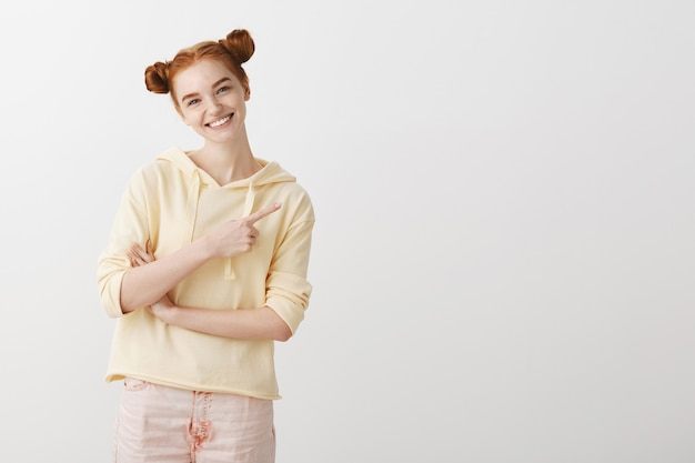 Friendly smiling redhead girl pointing finger right