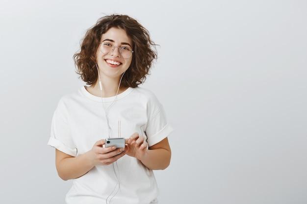 イヤホンで音楽を聴く、携帯電話を保持しているメガネでフレンドリーな笑顔の女性