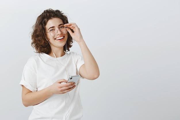 Дружелюбная улыбающаяся женщина в очках, держащая мобильный телефон, слушающая музыку в наушниках