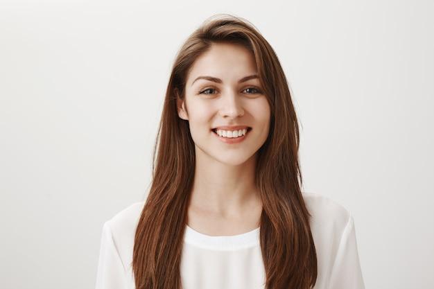 Donna sorridente amichevole che sembra contenta davanti