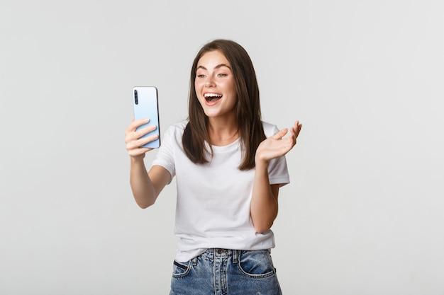 Дружелюбная улыбающаяся женщина видеозвонок и разговор на смартфоне счастливы, стоя белые.