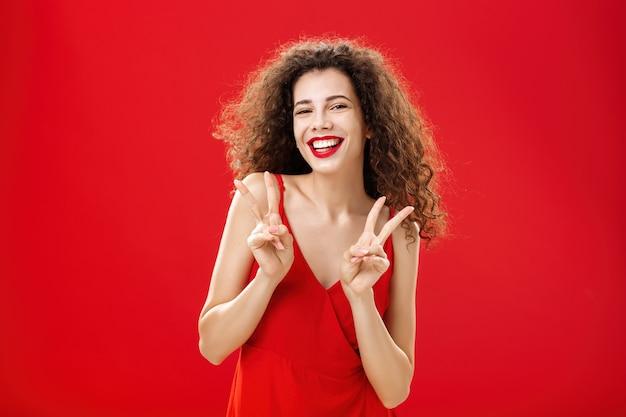 우아한 빨간 드레스와 저녁을 입고 곱슬 머리를 한 친절하고 사교적인 잘 생긴 행복한 소녀 ...