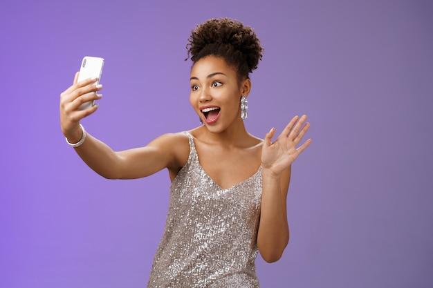 Amichevole elegante donna afro-americana sicura di sé in abito scintillante d'argento agitando palmo alzato ciao ciao gesto registrare video smartphone saluto seguaci di internet blogging durante la festa.