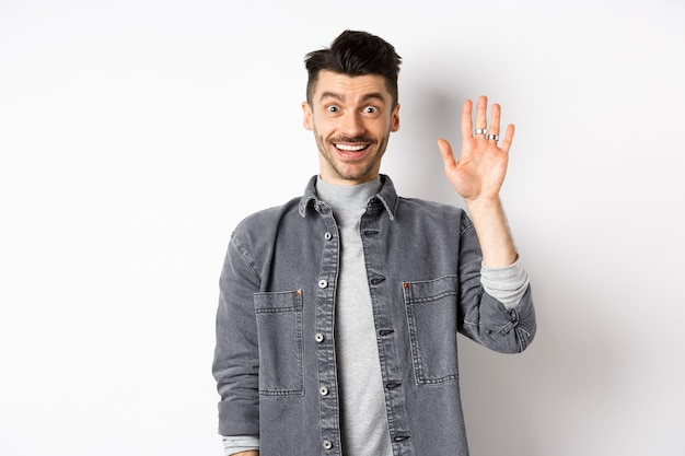Friendly stylish man saying hello and waiving hand, smiling cheerful, greeting you with hi gesture, standing on white background.