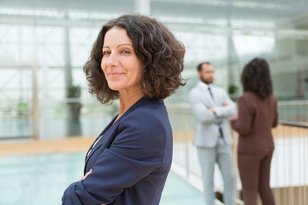 Дружественные успешной бизнес женщина позирует со скрещенными руками