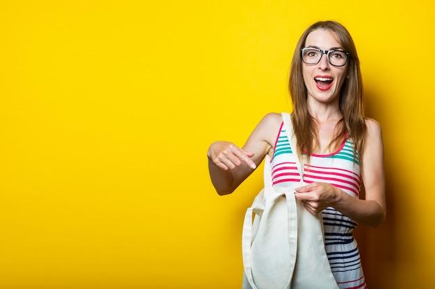 스트라이프 드레스와 안경, 친절한 놀란 어린 소녀는 노란색 배경에 린넨 가방을 가리 킵니다.