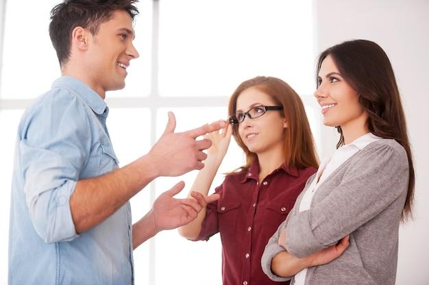 Дружеский разговор. обсуждение контракта в хорошем состоянии. две красивые молодые женщины обсуждают документ, пока двое мужчин общаются на заднем плане