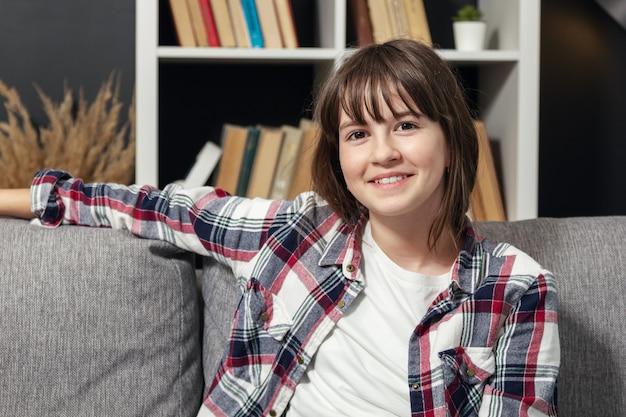 カメラ、正面図を見てソファの後ろに片方の腕でソファに座っているフレンドリーな10代の少女
