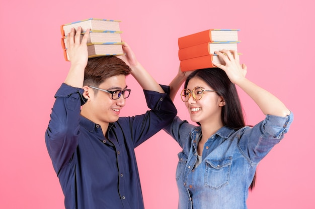 Friendly teenage man and woman place stack books on head