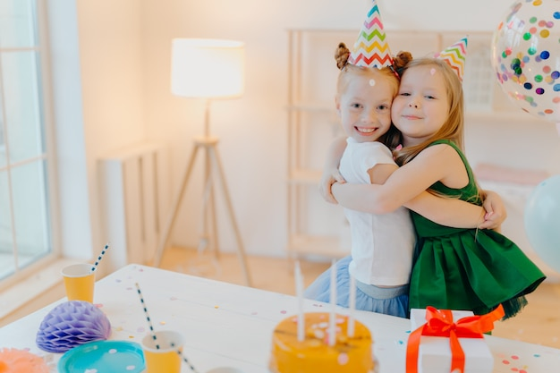 Friendly two girls embrace and have good relationship, stand near festive table with cake, celebrate birthday together, stand in living room.