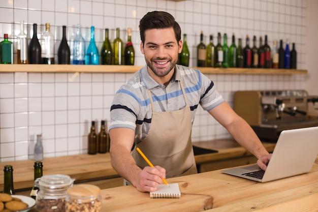 Приветливый официант. веселый позитивный красивый мужчина стоит у прилавка и улыбается вам, готовый делать заметки