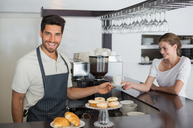 Friendly waiter giving coffee to a woman at coffee shop