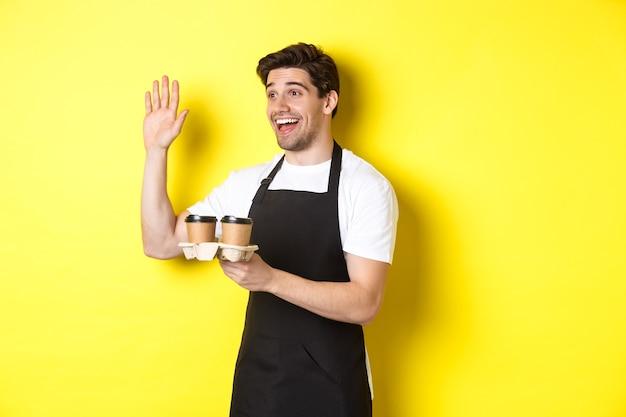 顧客に手を振って、持ち帰り用のコーヒーオーダーを持って、黒いエプロンで黄色の背景に立って、カフェでフレンドリーなウェイター。