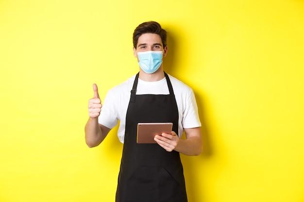医療用マスクと黒いエプロンでフレンドリーなウェイターが親指を立てて、デジタルタブレット、黄色の壁で注文を受けています