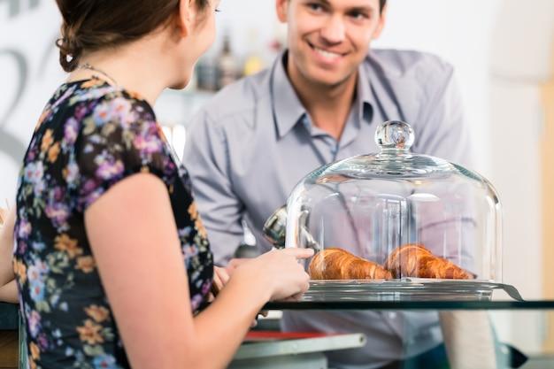 朝食のために若い女性の顧客に新鮮なフレンチクロワッサンを提供するフレンドリーなウェイター