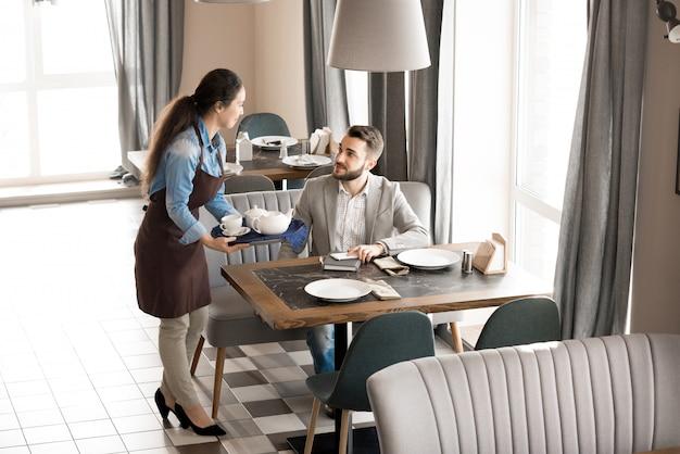 Дружелюбная официантка, дающая чай клиенту