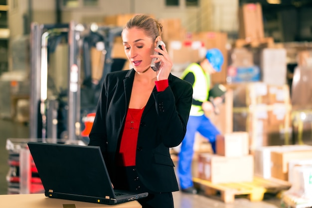 Friendly woman, dispatcher or supervisor using cell phone and laptop at warehouse of forwarding company, a forklift
