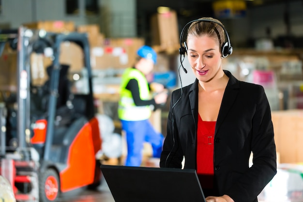 Friendly woman, dispatcher or supervisor using headset and laptop at warehouse of forwarding company, a forklift