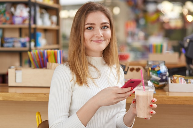Friendly woman with blonde hair, resting in cafe in morning, spends time with friends, drinking coctail and uses smartphone