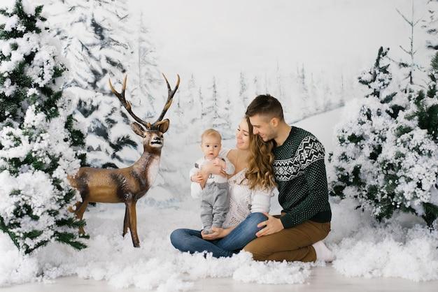 Дружная молодая семья: папа, мама и малыш на фоне зимней фотозоны в новогоднем лесу и олень