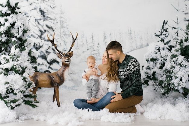 Friendly young family: dad, mom and baby on the background of the winter photo zone in the christmas forest and deer