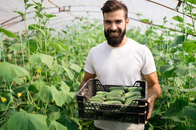 温室で働くフレンドリーな若い農夫
