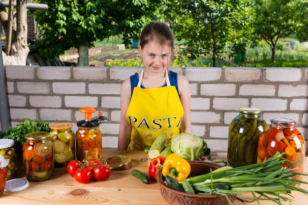 カメラに微笑んで大きな屋外のテーブルにガラスの瓶と新鮮な野菜の品揃えの後ろに立っている野菜を瓶詰めするフレンドリーな若い女の子