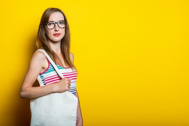 안경을 쓰고 친절한 어린 소녀는 노란색 배경에 그녀의 어깨에 린넨 가방을 보유하고 있습니다.
